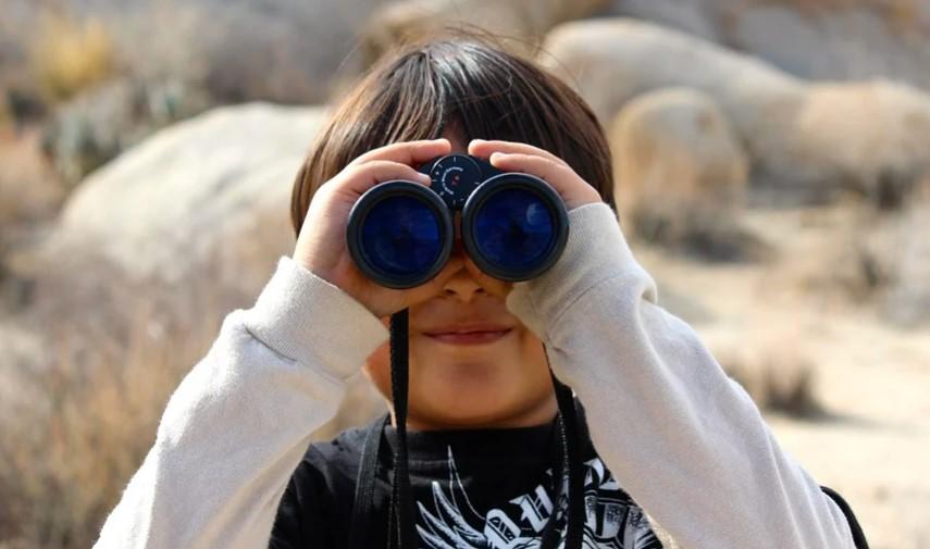 student watching through binoculars