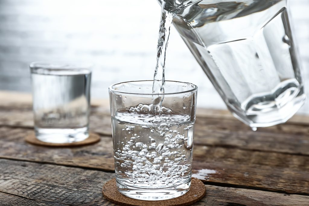 Pouring of fresh water from jug into glass on wooden table